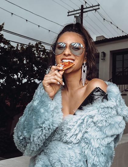 Shay Mitchell diện áo lông thú, ở nhà ăn pizza và uống rượu vang.
