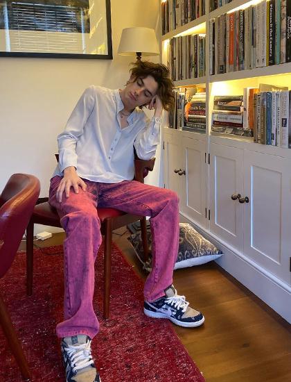 Tài tử Timothée Chalamet diện giày Nike hợp tác với rapper Travis Scott. Mặc sơ mi lụa cùng quần bò nhuộm màu hồng.