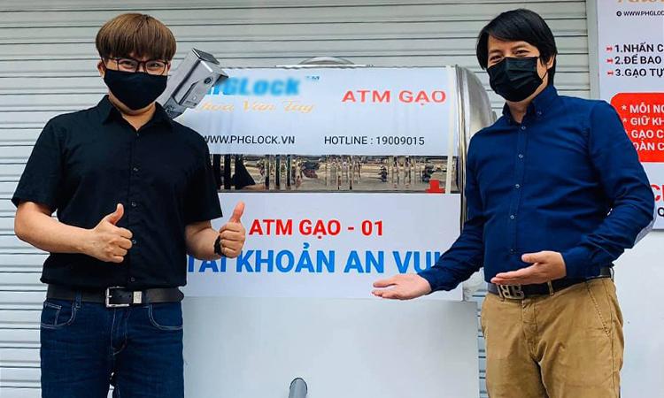 Đại Nghĩa (trái) và anh Hoàng Tuấn Anh - tác giả thiết bị - bên chiếc ATM gạo đầu tiên trong dự án của anh. Ảnh: Nhân vật cung cấp.