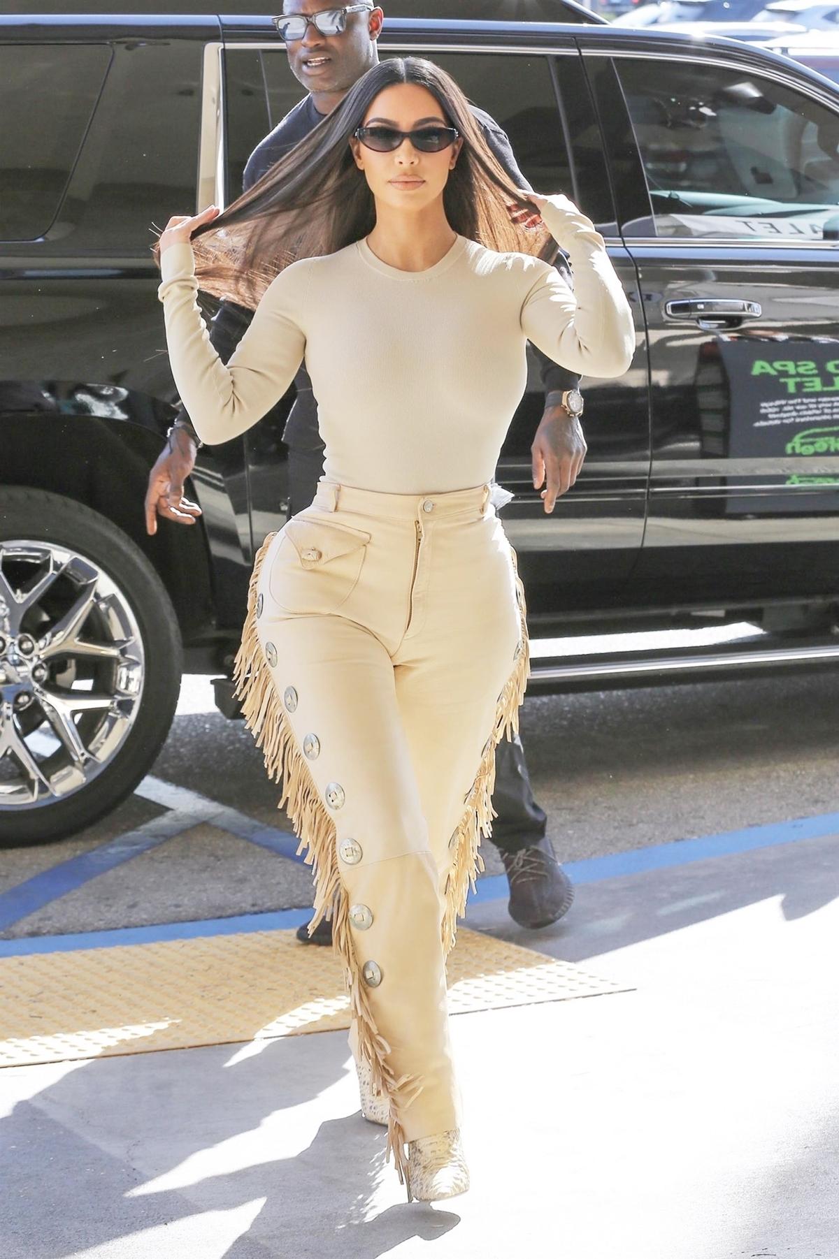 Ngày 6/3, Kim Kardashian xuất hiện trên đường phố Los Angeles (Mỹ) với phong cách cao bồi, tông nude chủ đạo. Cô mix quần tua rua của nhà mốtRoberto Cavalli với áo bodysuit. Ngôi sao truyền hình thực tế Mỹ thường gắn với hình ảnh gợi cảm, khoe da thịt. Tuy nhiên từ sau khi sinh con thứ tư, cô thay đổi gu mặc. Việc hạn chế sexy chủ yếu vì các con đang lớn dần. Kanye rất lo chúng bị ảnh hưởng xấu, Kim nói trên chương trìnhThe Real ngày 5/11/2019.Cô và rapper Kanye West hẹn hò từ tháng 4/2012, hết hôntháng 5/2014.