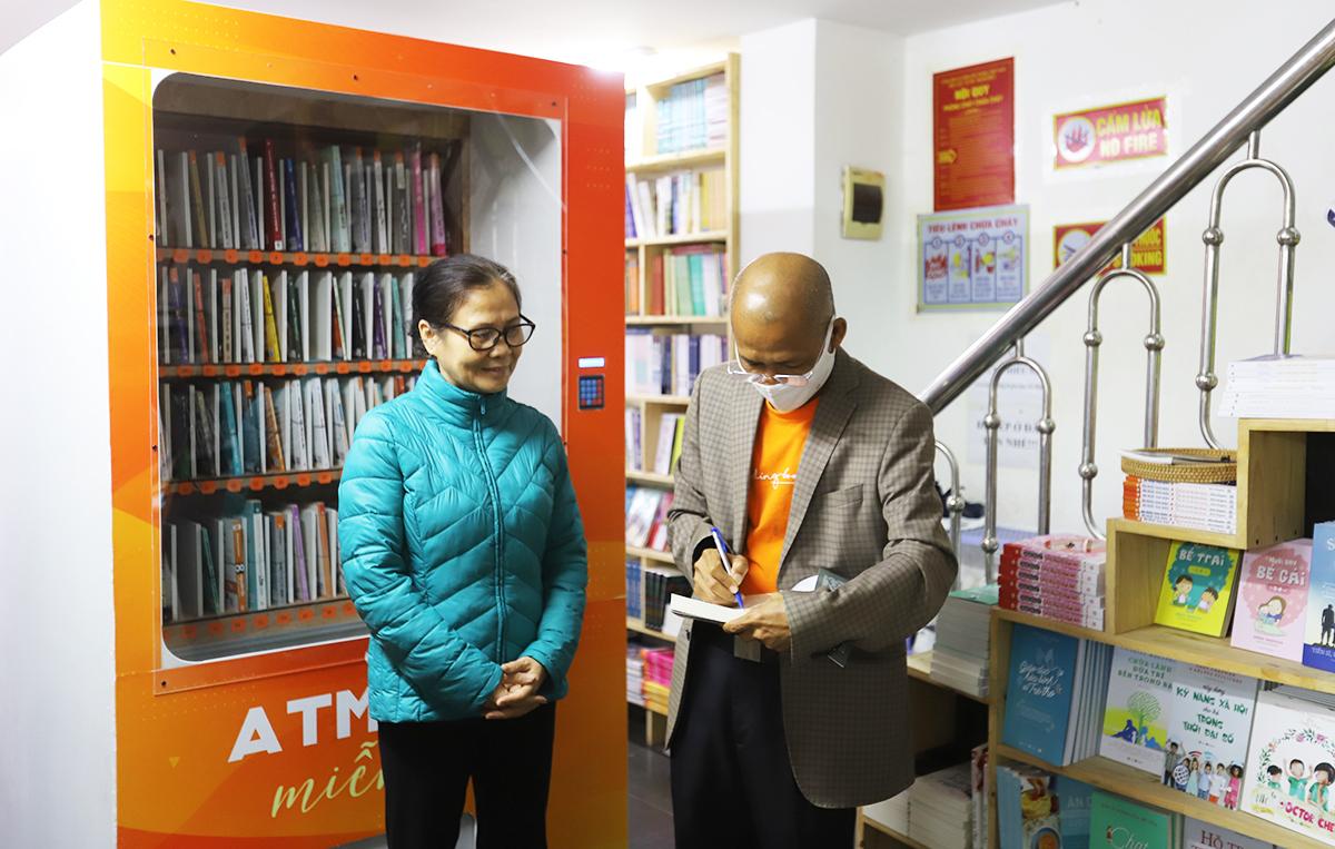 Ông Nguyễn Mạnh Hùng (phải) ký tặng một trong những độc giả đầu tiên nhận sách. Ảnh: Hiểu Nhân.