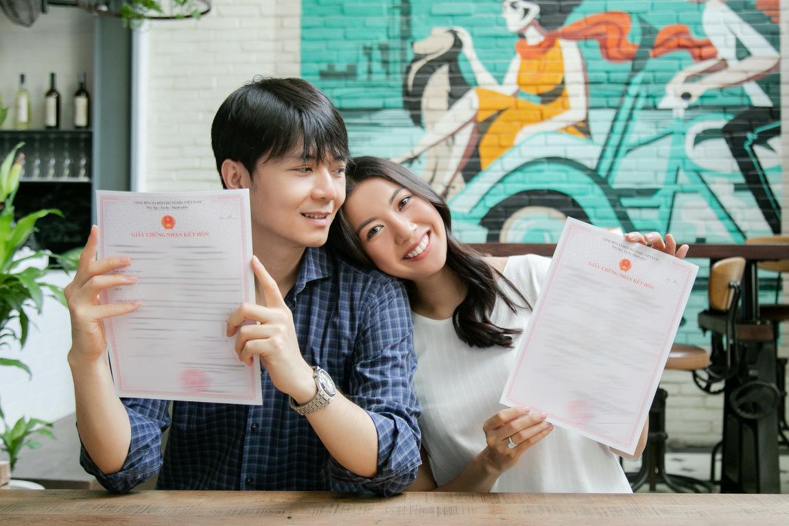 Đôi vợ chồng khoe giấy đăng ký kết hôn.