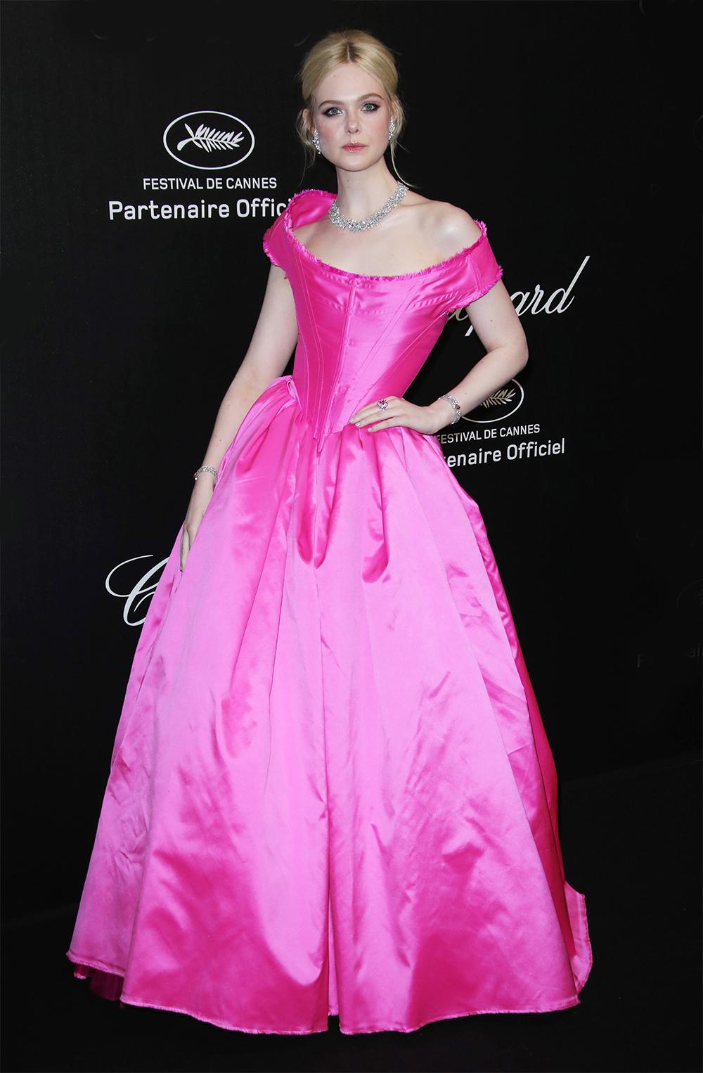 Elle Fanning được khán giả ví như công chúa Disney đời thực khi diện váy ballgown trễ vai màu hồng satin của nhà thiết kế Vivienne Westwood. Cô phối vòng cổ kim cương Chopard và loạt phụ kiện đính đá.