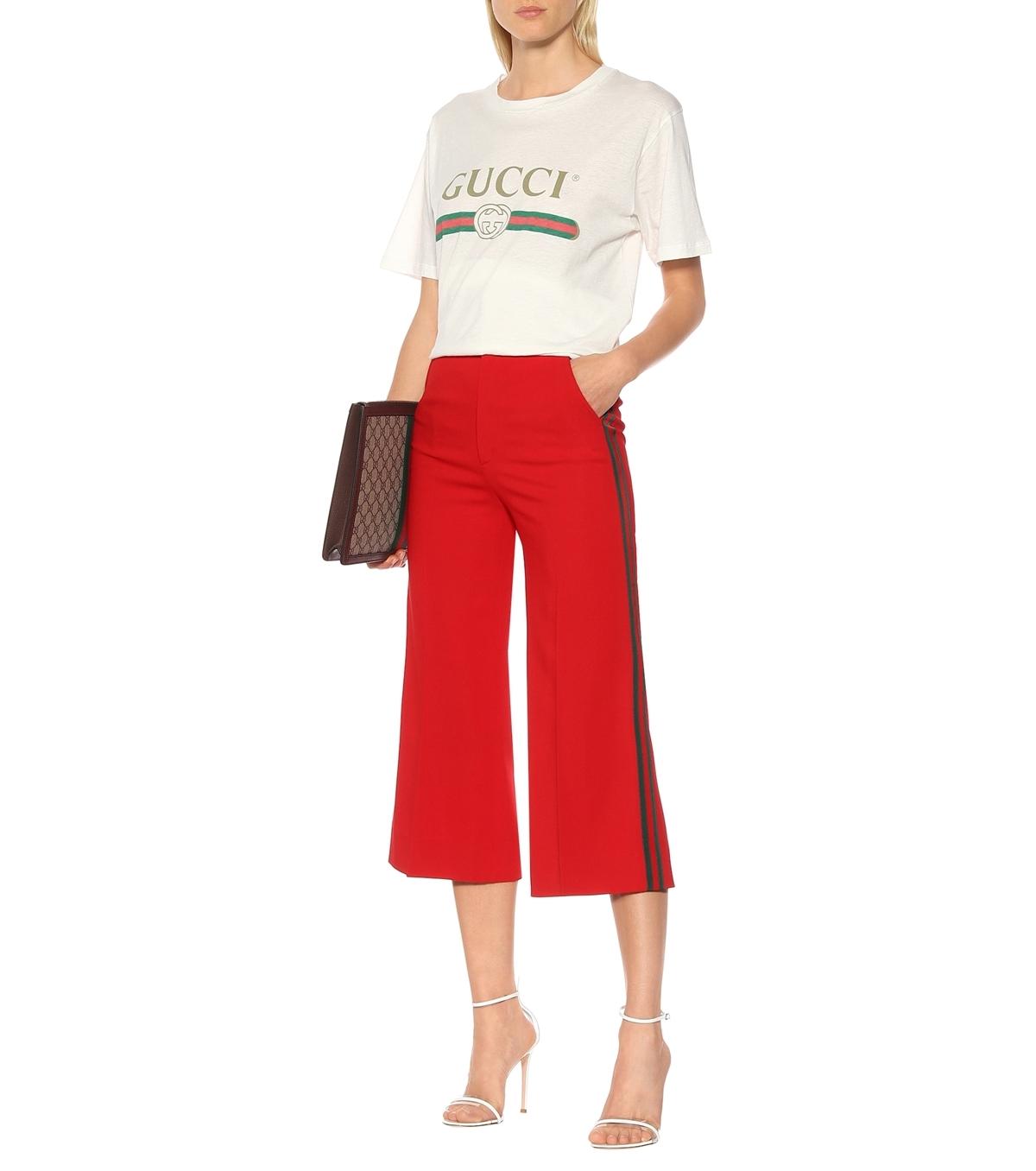 Thiết kế gam đỏ tươi, trang trí đường sọc xanh đỏ đặc trưng của Gucci đậm phong cáchretro. Nhà thiết kế gợi ý chị em kết hợp quần với áo thun, sandals và túi xách gắn logo cũng của Gucciđể tạoset đồ đồng điệu. Giá từ nhà sản xuất 1.300 AUD (gần 20 triệu đồng).