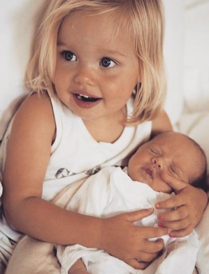 Cô bé chào đời ở Namibia (châu Phi) khi Angie đang thực hiện nhiều dự án nhân đạo với tư cách đại sứ Liên Hiệp Quốc. Cặp sao cũng không muốn sinh con tại Mỹ để tránh sự soi mói của truyền thông. Shiloh (trái, ba tuổi) bế em gáiVivienne mới chào đời. (Ảnh)
