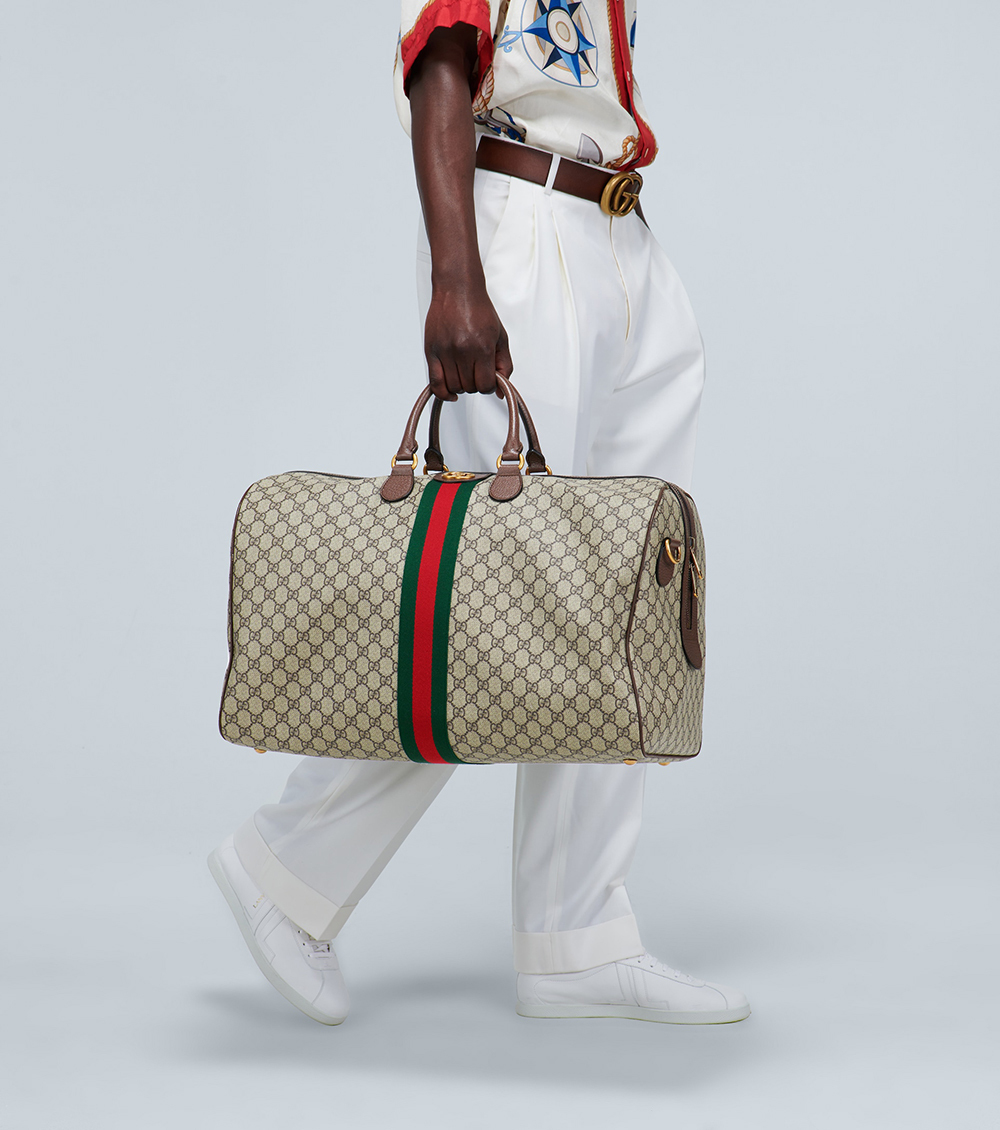 Hãng Gucci tiếp tục lăng xê họa tiết GG trên màu vải be của dòng túi cầm tay cỡ lớn. Hàng kẻ sọc xanh đỏ chạy dọc thân túi hoàn thiện phong cách đặc trưng của hãng. Dây đeo có thể tháo rời và khóa an toàn, giá 1.550 EUR.