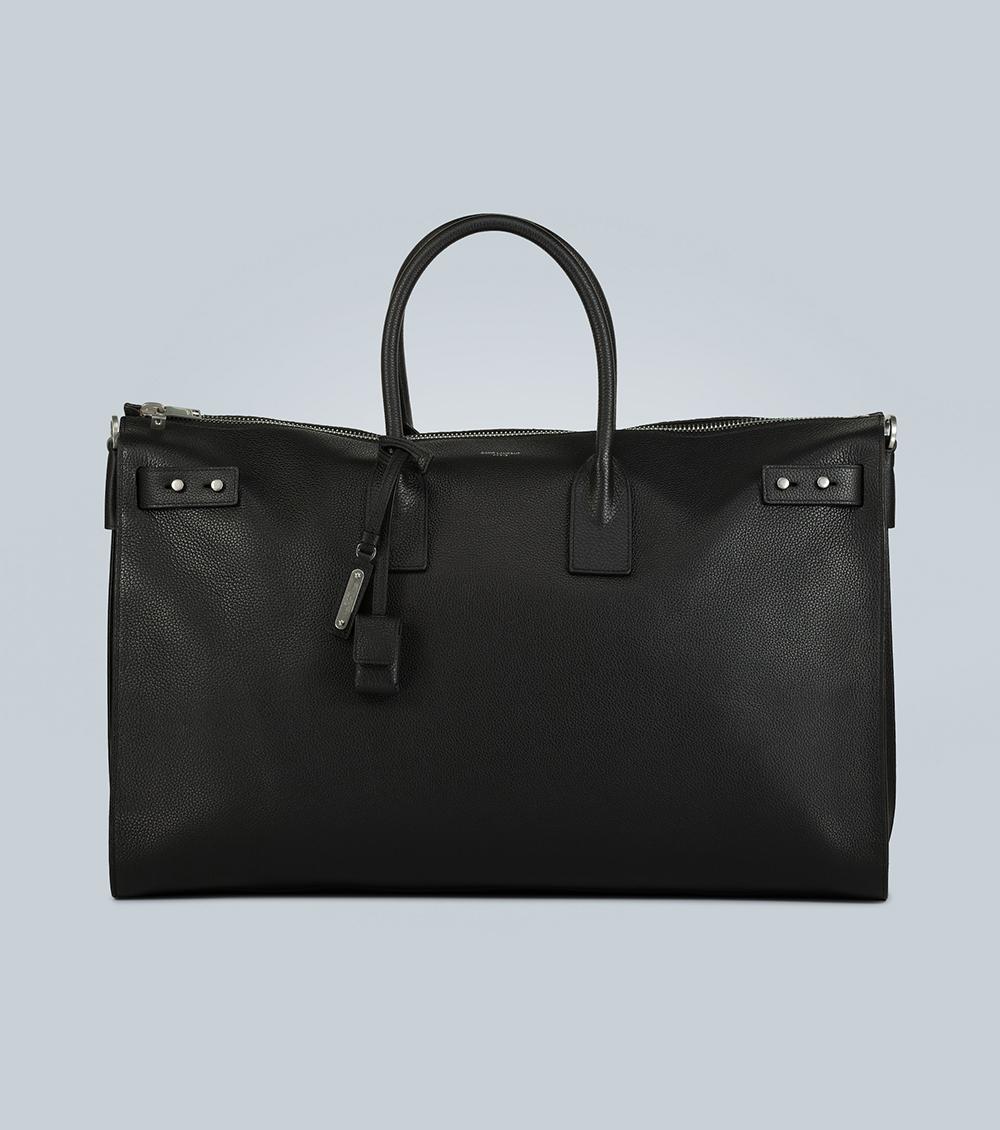 Saint Laurent sử dụng chất liệu da bê màu đen cho túi du lịch giá 2.059 EUR. Nhà sản xuất trang bị đai điều chỉnh kích cỡ ở hai bên và túi nhỏ bên trong.