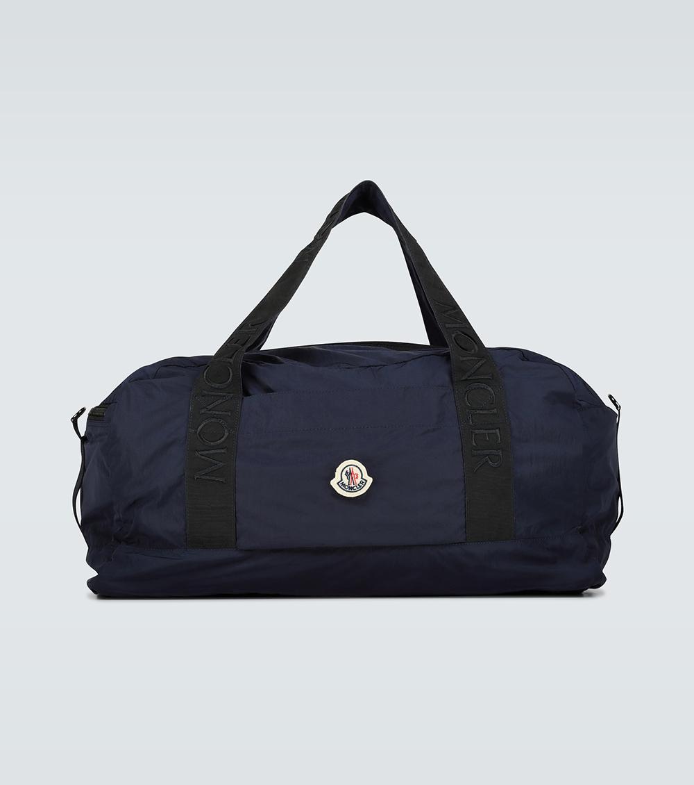 Thiết kế màu xanh hải quân, thêu logo Moncler trên dây đai, giá 445 EUR. Sản phẩm làm từ vải dệt kỹ thuật với đặc tính nhẹ, không thấm nước, bên trong chứa túi zip tiện ích để phân loại vật dụng.