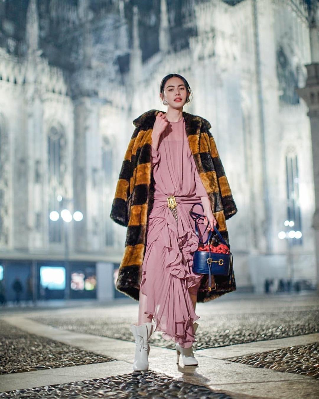 Tại Tuần thời trang Milan, người đẹp mặc phá cách với ba gam đối lập. Cô mix váy bèo nhún hồng, áo khoác vàng, đen và túi bucket xanh lam của Gucci.
