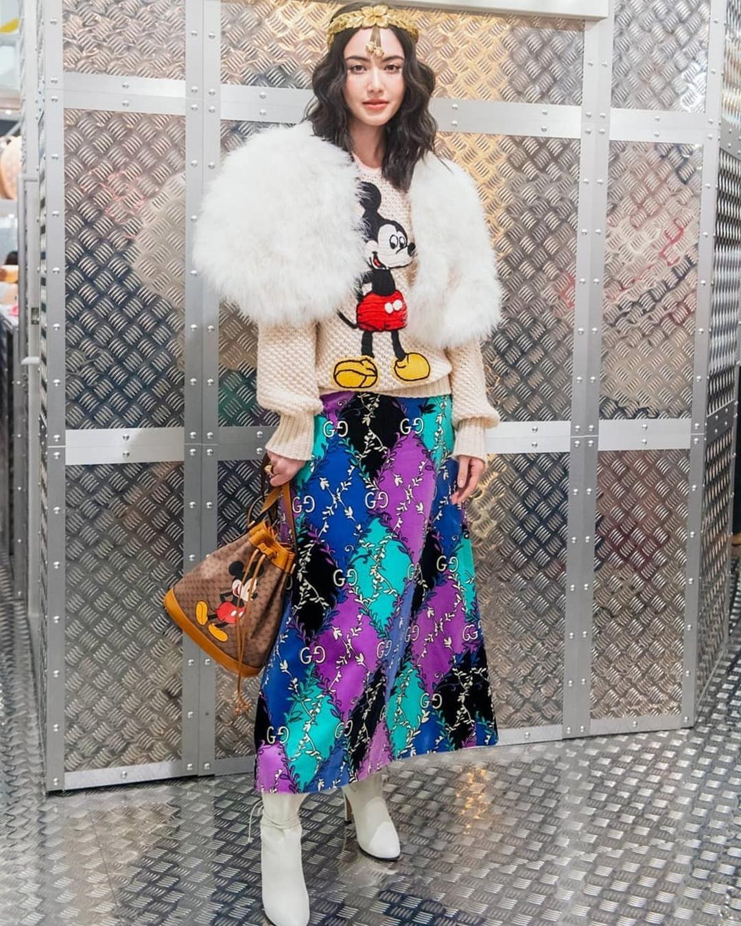 Mỹ nhân Thái Lan tiếp tục lăng xê trang phục của Gucci trong một sự kiện. Cô xách túi xô họa tiết chuột Mickey hơn 43 triệu đồng, đồng điệu áo len, tạo điểm nhấn với phụ kiện đội đầu mô phỏng vòng nguyệt quế và áo lông trắng.