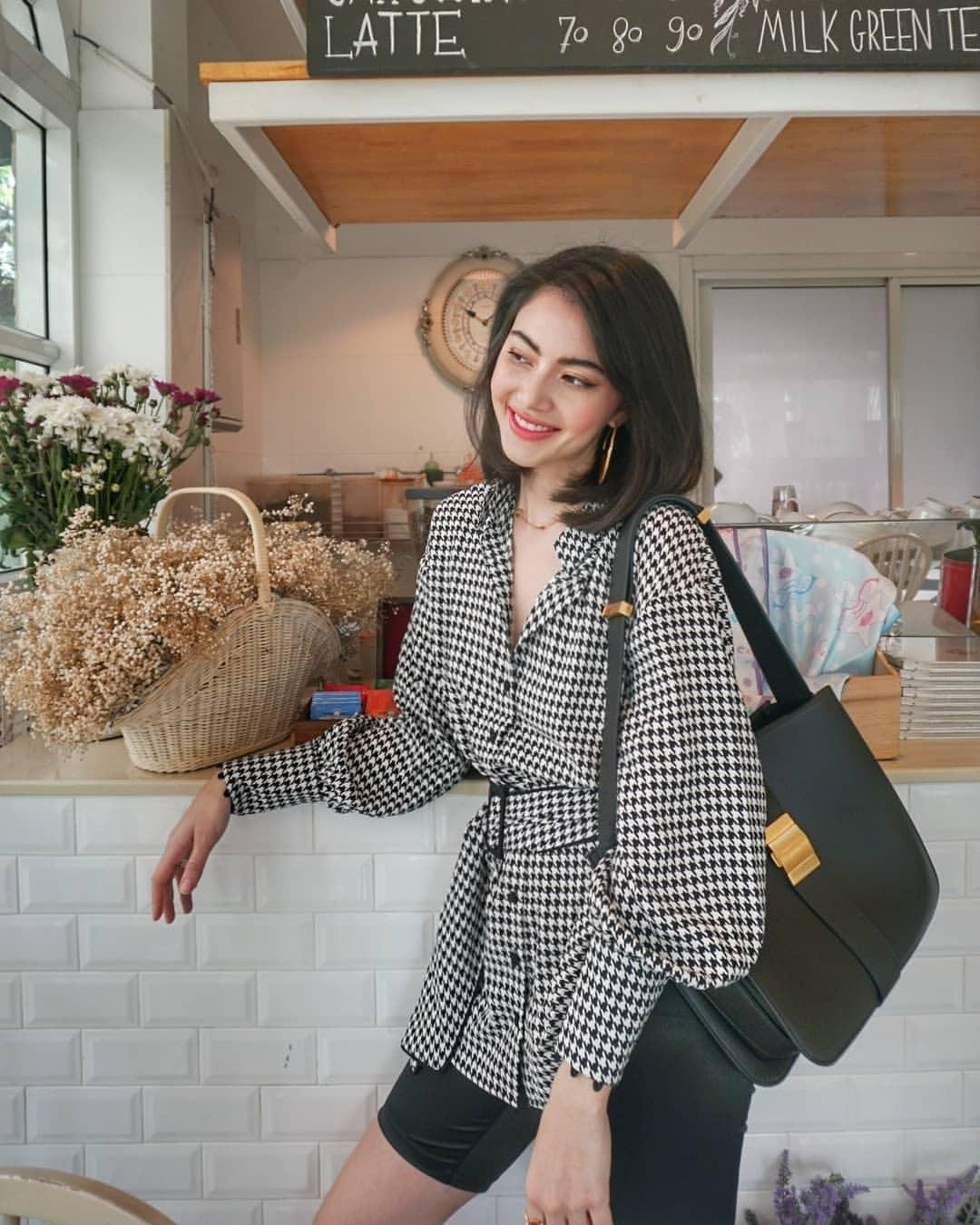 Diễn viên được khen phong cách với set đồ đen trắng, nhấn vào túi đeo vai bản to Bottega Veneta khi đến quán cà phê do cô làm chủ.