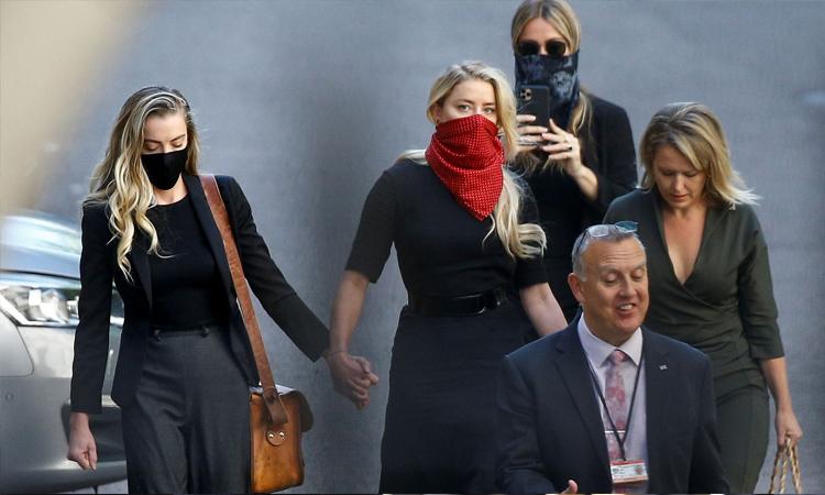 Amber Heard (khẩu trang đỏ) tới làm chứng cho phiên tòa Johnny Depp kiện công ty truyền thông gọi anh là kẻ đánh vợ. Ảnh: Sky News.