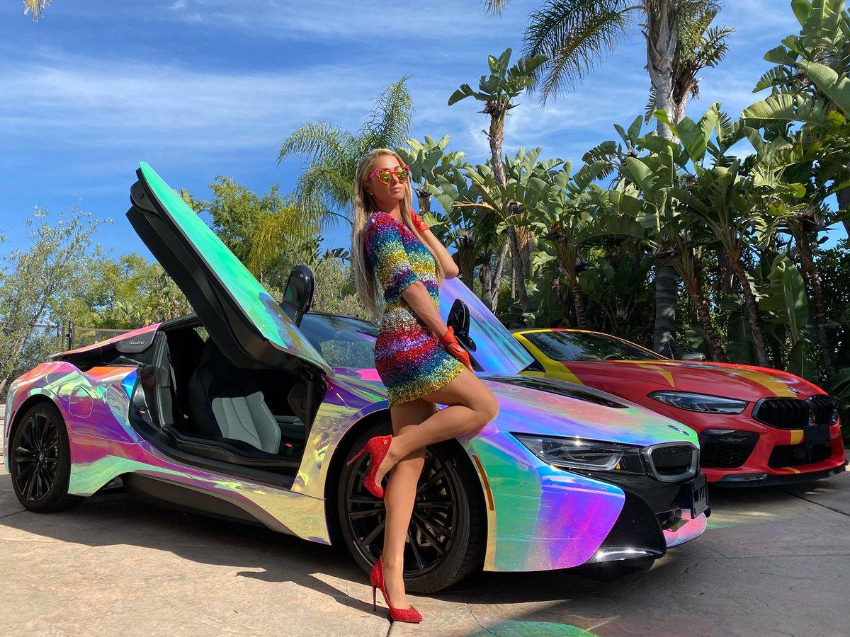 Ngày 26/6, Paris Hilton mặc thiết kế đa sắc từ nhà mốt Alice & Olivia, tạo dáng bên chiếc xe BMW sơn cầu vồng nhằm ủng hộ cộng đồng LGBT. Cô phối phụ kiện gam đỏ đậm như kính mắt Rad & Refined, giày đính pha lê Phillip Plein và găng tay không ngón Chanel.