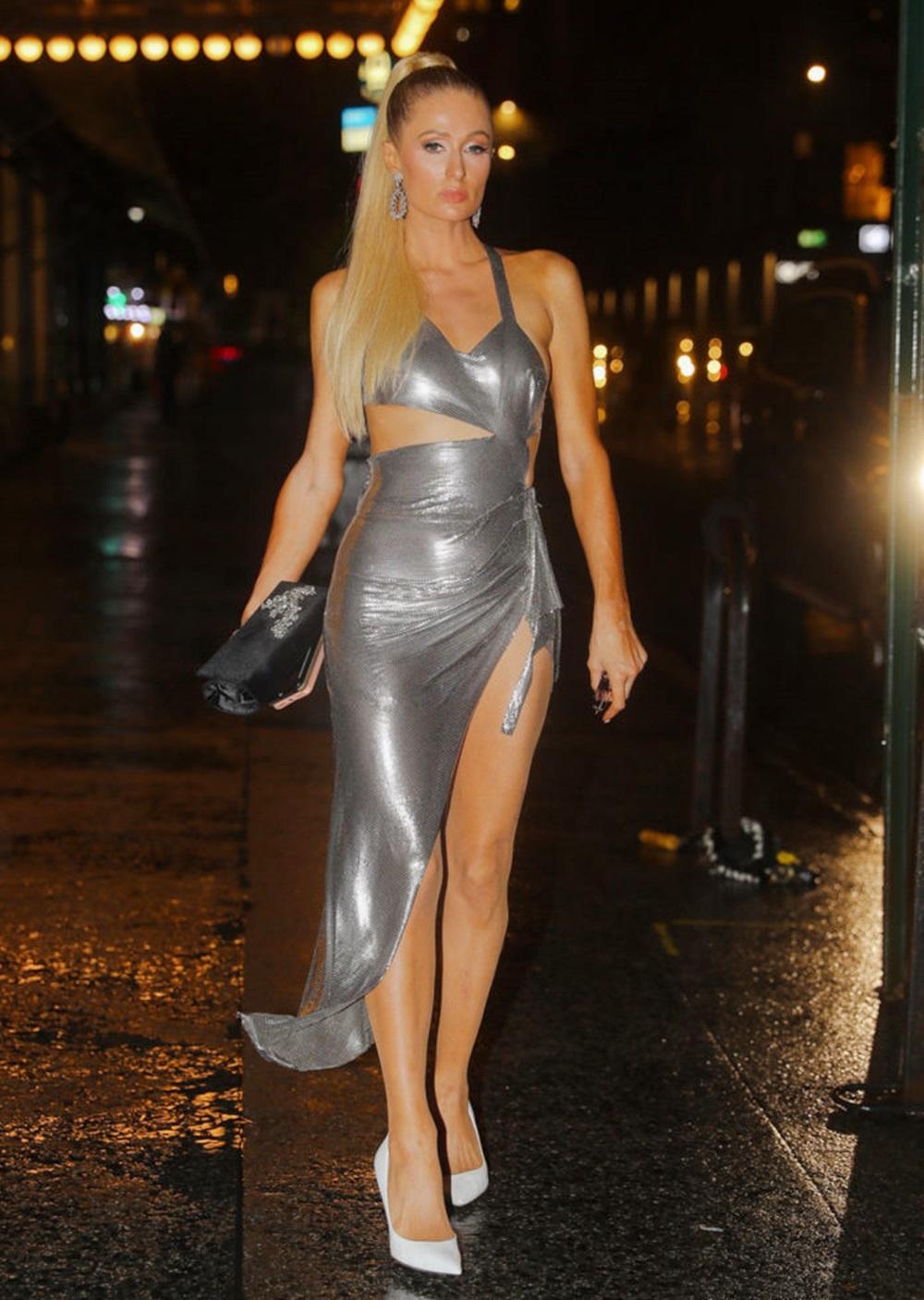 Cô cột tóc đuôi ngựa, diện đầm ánh bạc cắt khoét eo của Fannie Schiavoni ở sự kiện Kkw X Winnie năm 2019. Cô phối giày trắng Sergio Rossi, nhấn vào clutch đen Cleopatra Crystal và khuyên tai bản to.