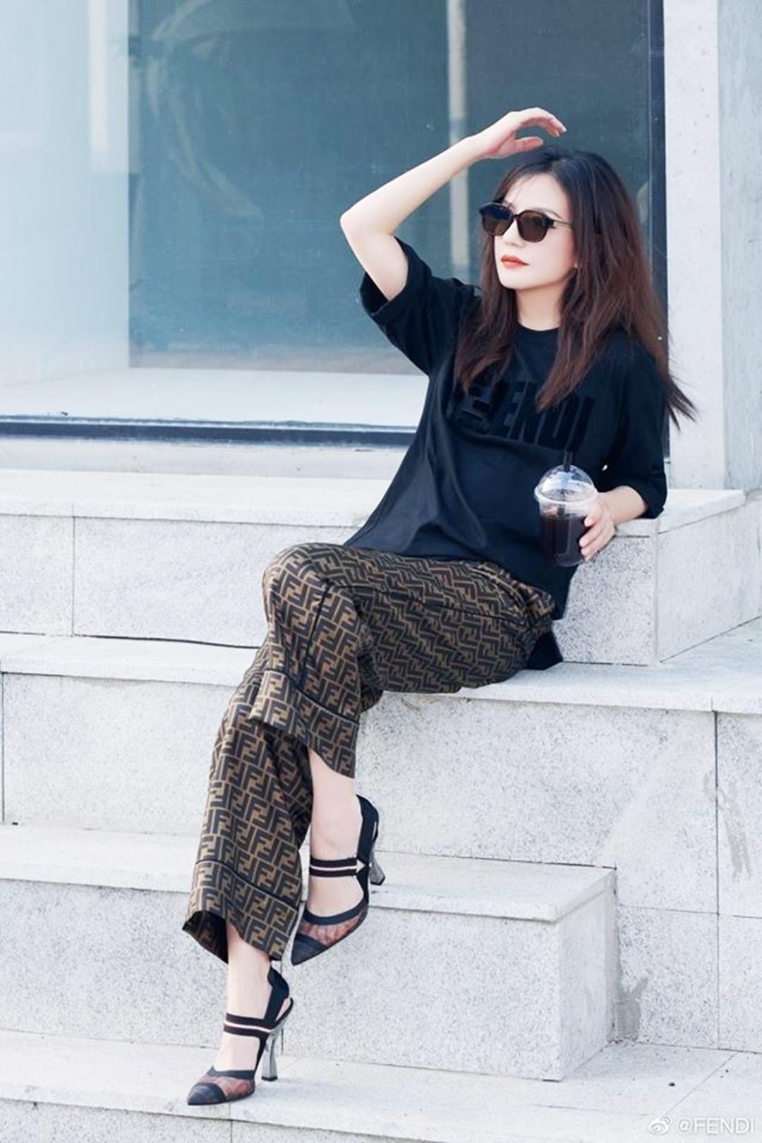 Cô khoe phong cách trên phố với cây Fendi gồm: áo thun đen, quần lụa hoa tiết FF đặc trưng nhà mốt và giày mũi nhọn xuyên thấu.
