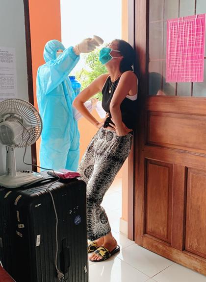 Minh Tú tạo dáng người mẫu hài hước khi được cán bộ y tế đến đo thân nhiệt. Ảnh: Facebook.