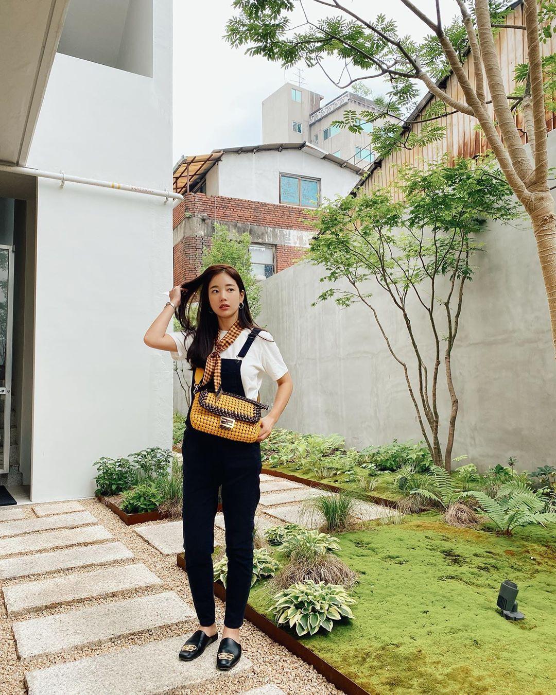 Cô khoe phong cách với túi Baguette cỡ lớn - bản giới hạn đắt thứ hai của Fendi ra mắt đầu năm, giá 9.000 USD (212 triệu). Thiết kế đan cài hai chất liệu da nappa nâu (làm từ da cừu) và lông chồn. Logo hai đặc trưng thương hiệu làm bằng kim loại, bề mặt sáng bóng.