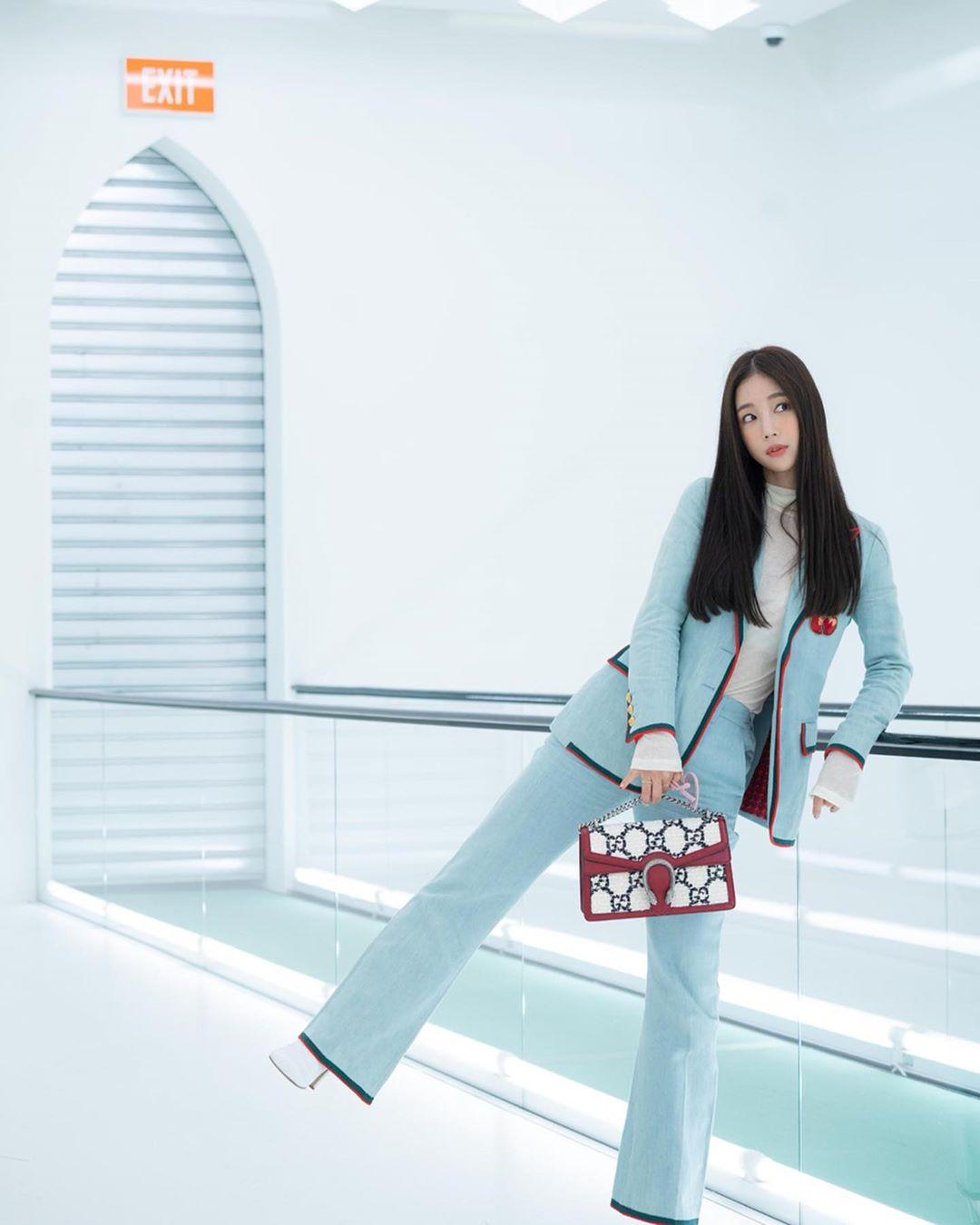 Cô tạo dáng với túi Gucci họa tiết tại Tuần thời trang Milan tháng 9 năm ngoái. Đường viền đỏ phụ kiện đồng điệu với đường viền trang phục.