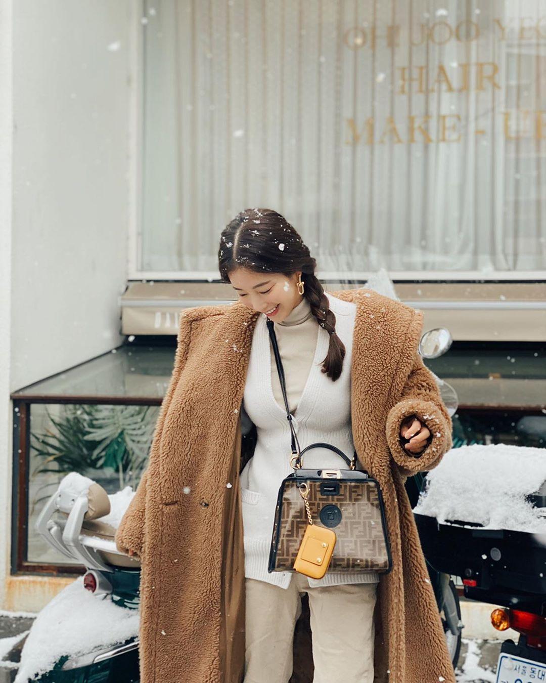 Truyền thông Hàn nhận xét Ki Eun Se sành điệu, như bước ra từ tạp chí khi dạo chơi tuyết ở Seoul vài ngày trước đó. Cô mang túi đeo chéo họa tiết FF gam nâu chủ đạo của Fendi.