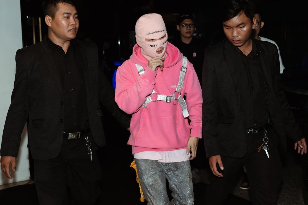 Tại một dịp khác, anh xuất hiện với mũ trùm đầu bịt kín mặt, áo hoodie hồng và quần denim lấp lánh. Điểm nhấn bộ cánh nằm ở chiếc đai bảo hộ theo mốt đeo yên cương rộ lên từ năm 2015.