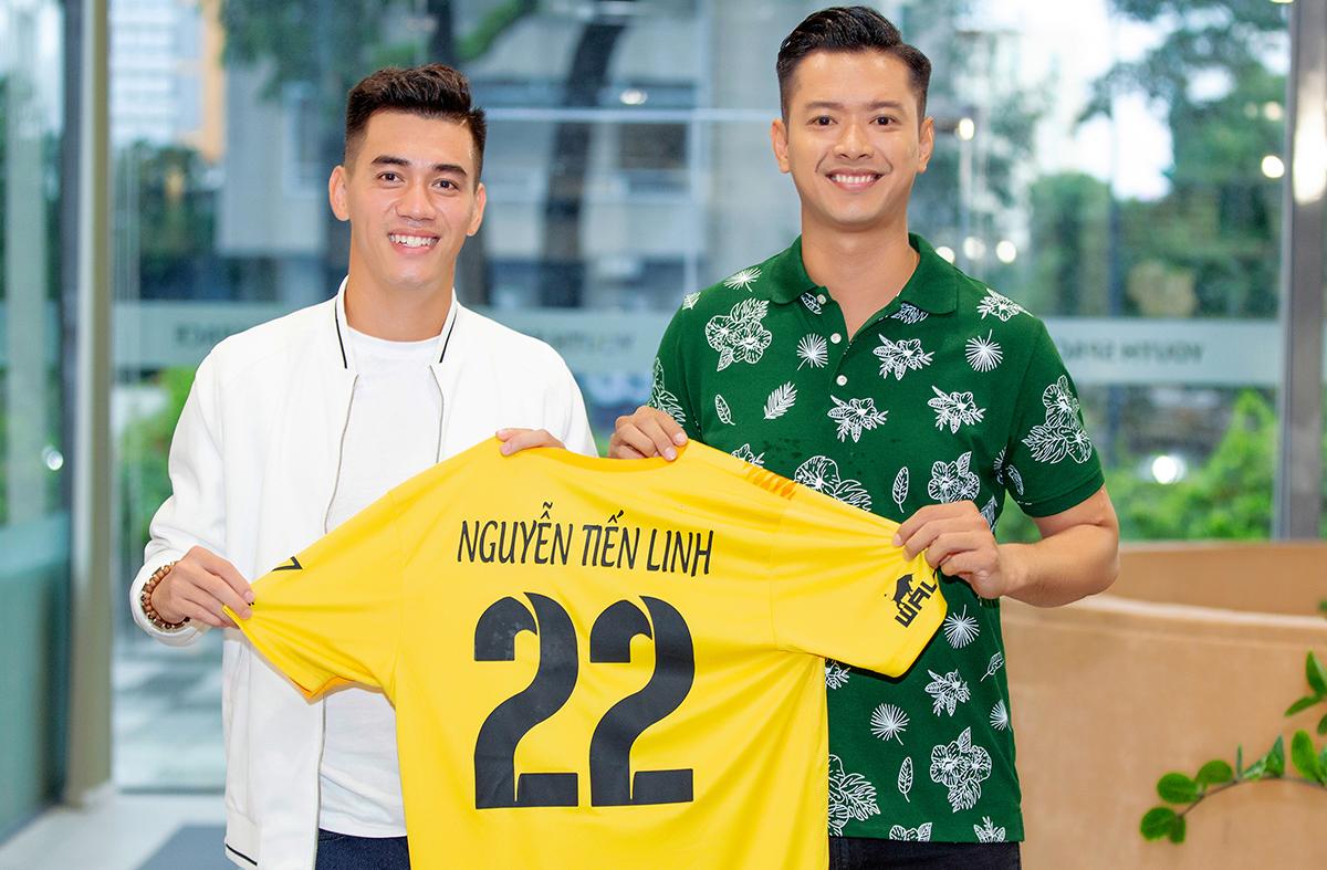 Tuyển thủ Nguyễn Tiến Linh (trái) nhận áo thành viên của Câu lạc bộ bóng Nghệ sĩ từ đội trưởng - người mẫu Hồ Đức Vĩnh (phải). Ảnh: Vĩnh Đức.