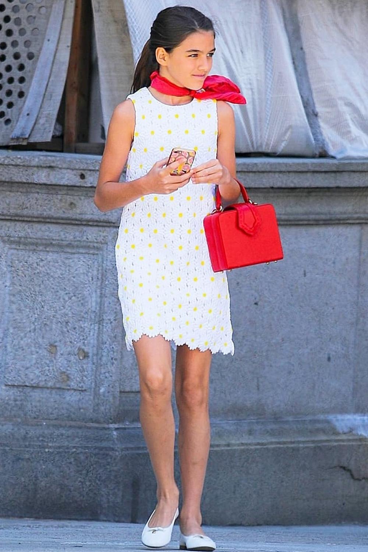 Khán giả ví Suri Cruise như tiểu công nương Diana với váy thêu hoa trắng Dolce & Gabbana, nhấn vào khăn quàng cổ và túi xách hình hộp gam đỏ.