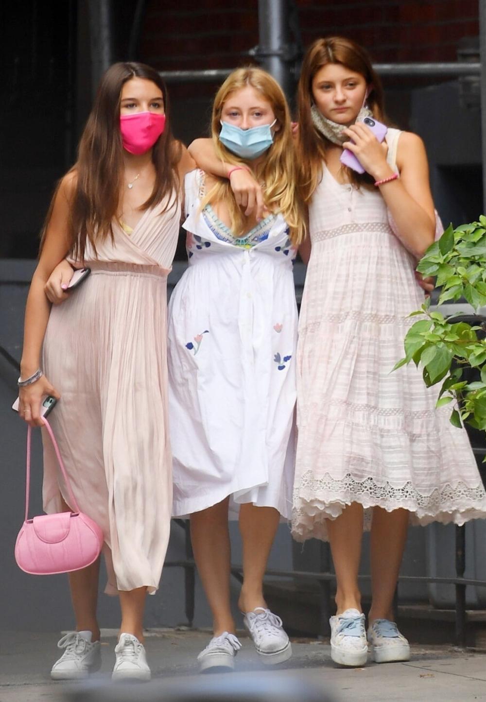 Trước đó 3 ngày, Suri (ngoài cùng, tay trái) xuất hiện trên phố, đi ăn trưa cùng bạn với váy dây màu nude, tôn trang phục bằng túi đeo vai hồng nhạt.