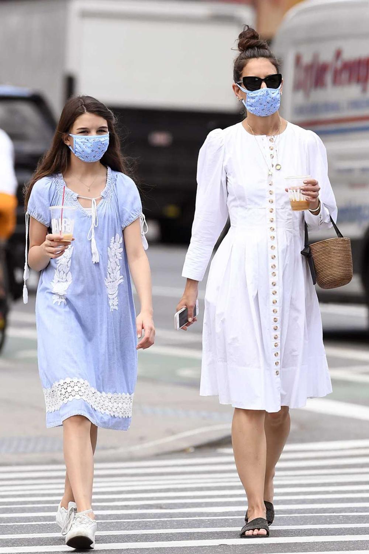 Cô bé diện váy xanh thêu ren, phối giày thể thao trắng đi chơi cùng mẹ hồi tháng 6. Suri đón sinh nhật tuổi 14 vào ngày 18/4, hiện cao quá vai mẹ (Katie Holmes cao 1,75 m). Diễn viên cho biết không lo lắng khi con gái bước vào tuổi dậy thì.