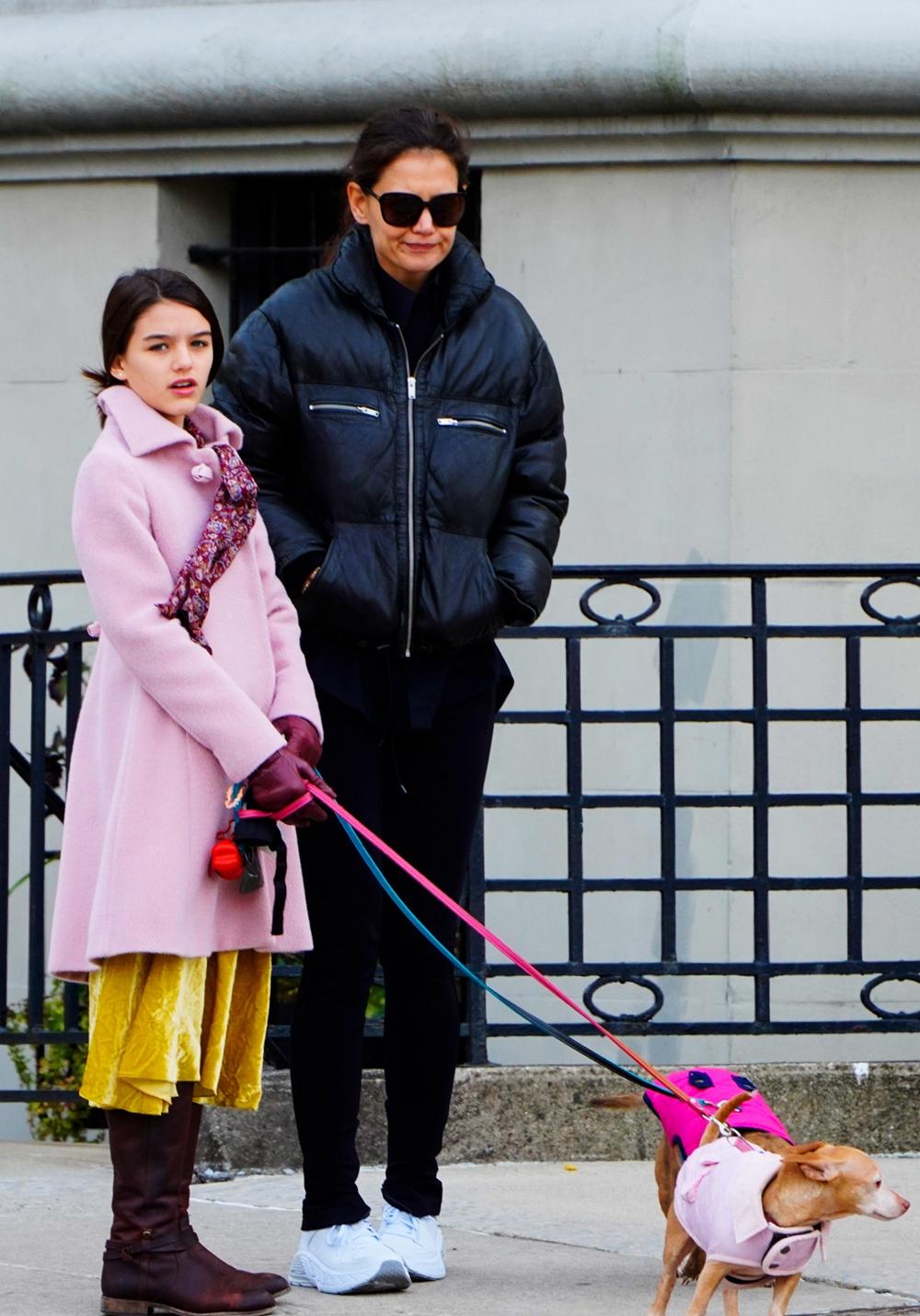Suri dắt cún đi dạo cùng mẹ trong trang phục phối layer, điểm nhấn là áo khoác hồng dài đến đầu gối, để lộ chân váy nhung vàng. Cô bé tô điểm phong cách bằng găng tay màu đỏ tía, khăng quàng cổ hoa văn cổ điển và boots da lộn giữ ấm.