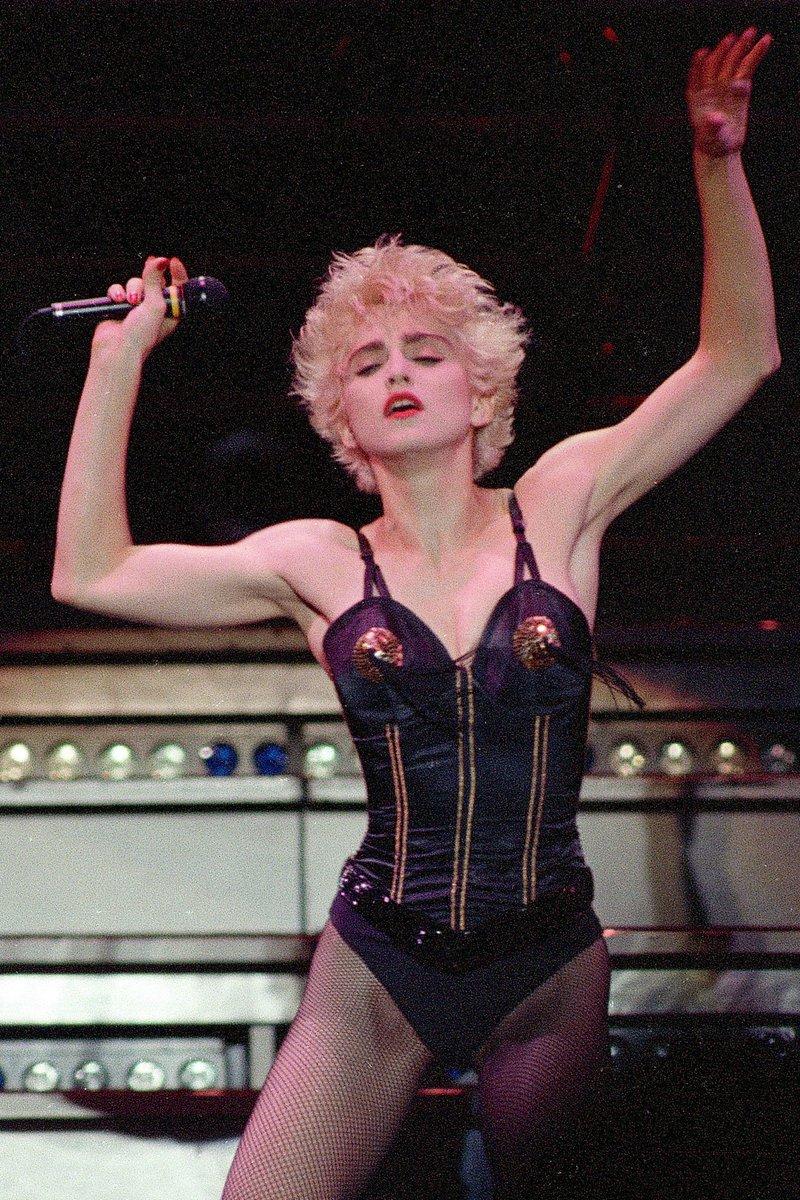 Trong chuyến lưu diễn Whos That Girl năm 1987, Madonna bước lên sân khấu với corset hình nón của Jean Paul Gaultier. Phần trang trí bằng vàng được hoàn chỉnh với các sợi tua rua ở đỉnh ngực. Ca sĩ diện nó với quần tất lưới mắt cá, tạo nên vẻ sexy hoang dại. Ảnh: Ảnh chụp màn hình Twitter Classic Madonna.