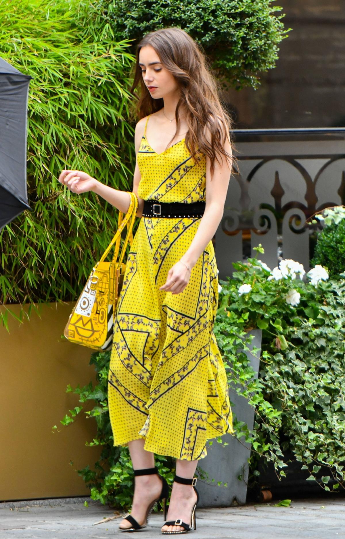 Người hâm mộ nhận xét set áo lụa, chân váy midi màu vàng tươi từ hãng Ganni làm bật làn da trắng của Lily Collins. Cô xách túi Patricia Field họa tiết tông vàng, mang thắt lưng Rag & Bone tạo sự đồng điệu với sandals. Ảnh: The Mega Angecy