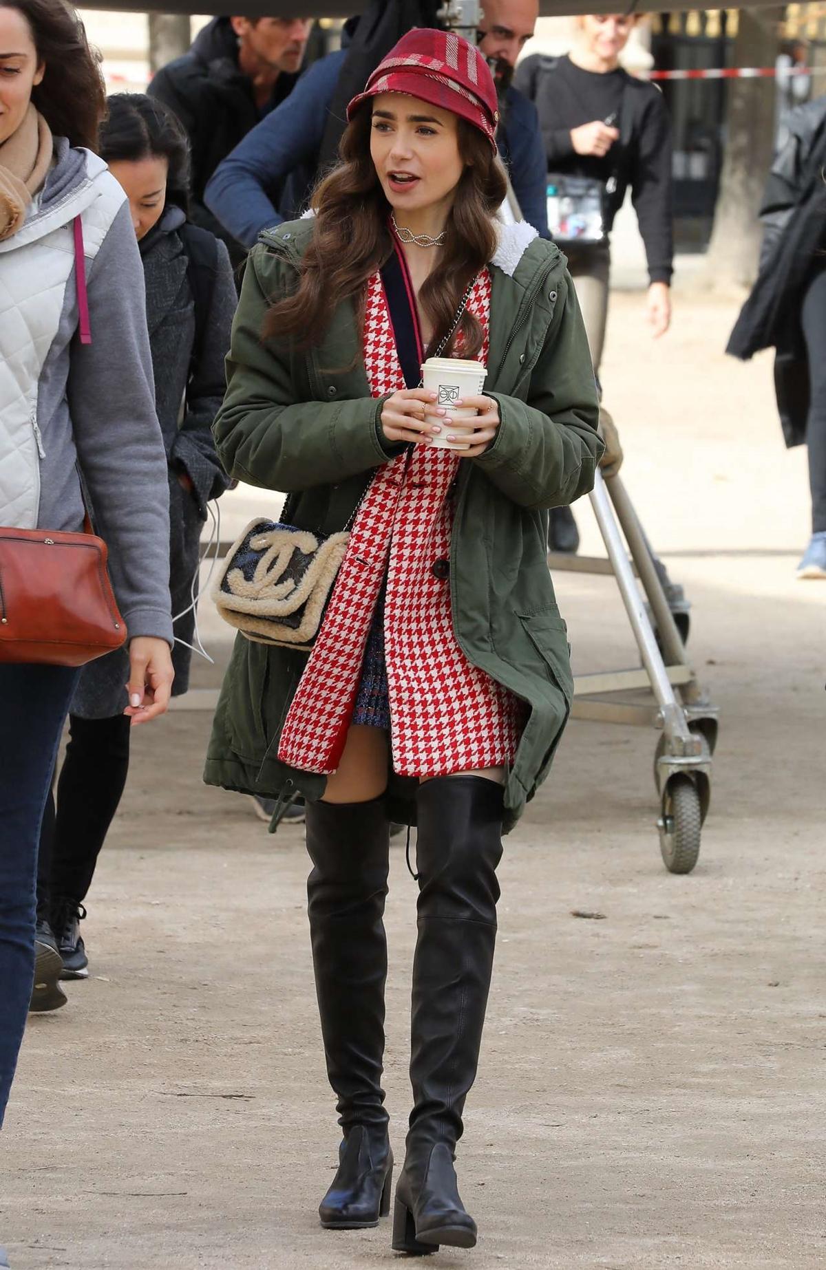 Cô thu hút ống kính khi diện các thiết kế đậm chất cổ điển gồm áo khoác Zara kẻ ô, mũ sọc đỏ, túi đeo vai gắn lông cừu Chanel, mix thêm áo khoác quân đội, boots cao lên gối, hài hòa nét thanh lịch và năng động. Ảnh: Splashnews