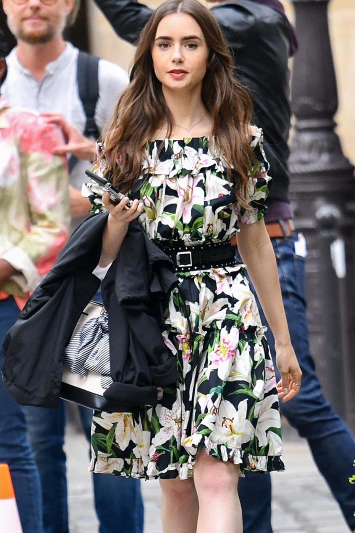 Trong cảnh quay khác, cô tiếp tục mang túi cầm tay Aldo với váy hoa trễ vai Dolce & Gabbana. Nhân vật tôn vóc dáng với thắt lưng Rag & Bone, giày màu hồng cánh sen Christian Louboutin. Ảnh: Splashnews