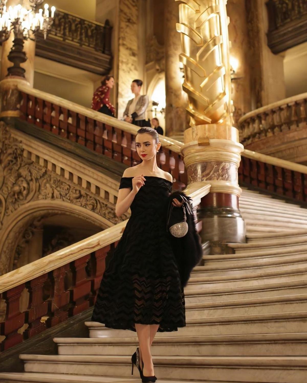 Nhiều khán giả nói Lily Collins gợi nhớ hình ảnh minh tinh Audrey Hepburn khi diện đầm đen Christian Siriano, đầu đội chuỗi vòng đá quý, tô điểm bằng clutch dát pha lê trong cảnh dự tiệc tối. Ảnh: Netflix