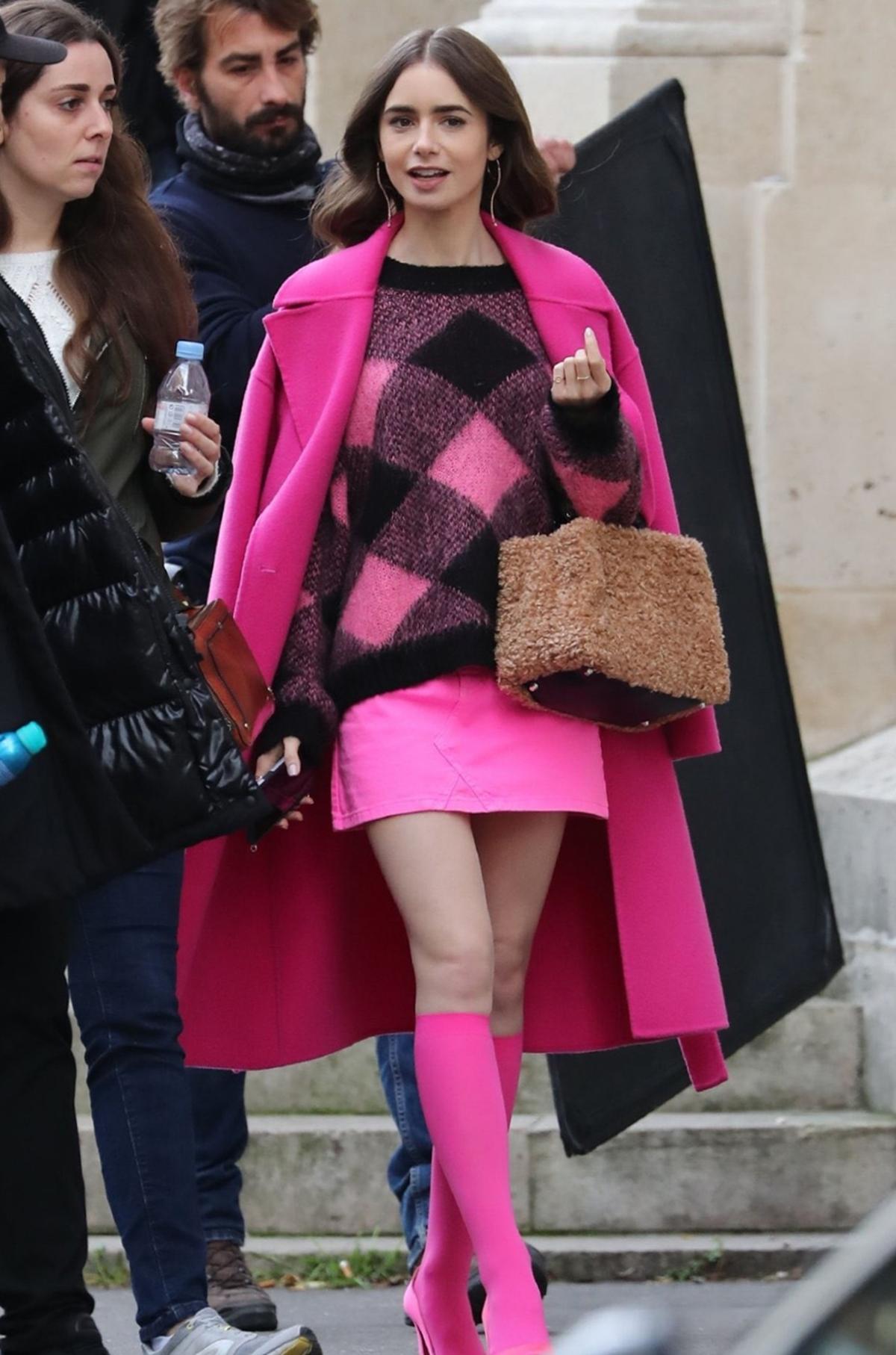 Lily Collins thu hút truyền thông khi diện cây hồng trong buổi quay phim trên đường phố Paris. Cô kết hợp áo khoác Kenzo, bên trong mặc áo len Sandro, phối chân váy denim của Chiara Ferragni. Ảnh:  BackgridUSA