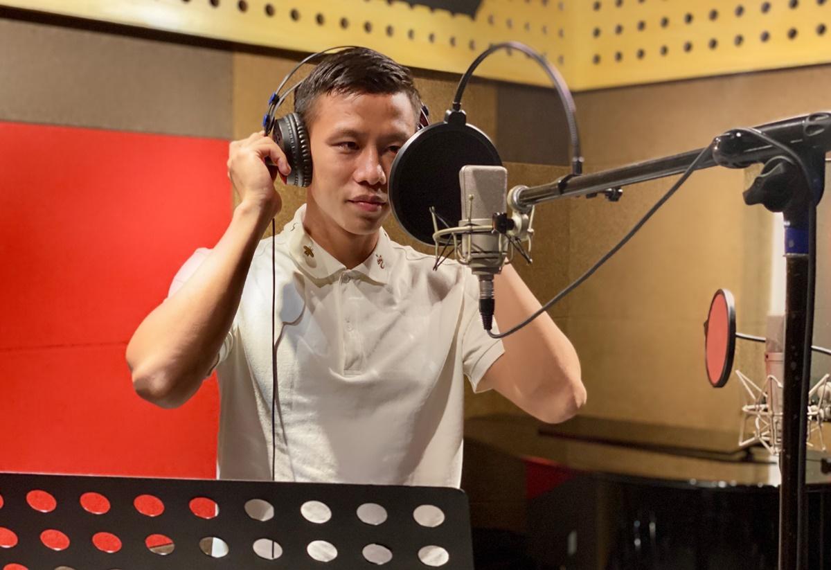 Cầu thủ Quế Ngọc Hải trong phòng thu. Anh được ca sĩ Tuyết Nga hướng dẫn trong suốt quá trình thu âm ca khúc. Ảnh: Tuyết Nga.
