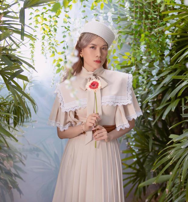 Váy xếp ly kiểu cổ vuông diềm đăng ten của nhà thiết kế Hoàng Tony phối mũ pillbox, mạng lưới, giúp ca sĩ toát lên vẻ quý tộc.