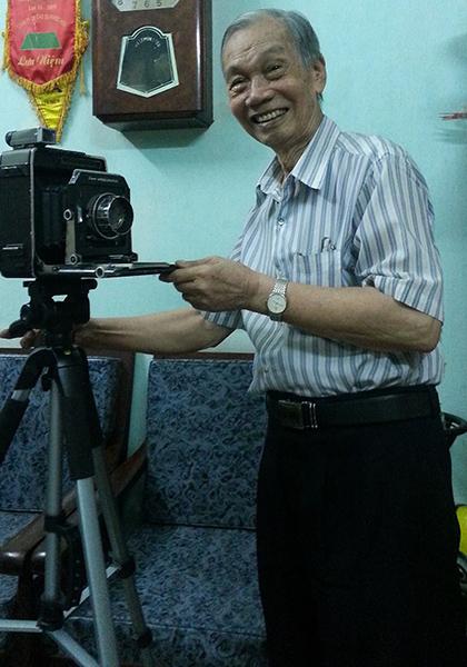 Nhiếp ảnh gia Đinh Tiến Mậu sinh thời bên máy ảnh huyền thoại. Ảnh: Phương Nam.