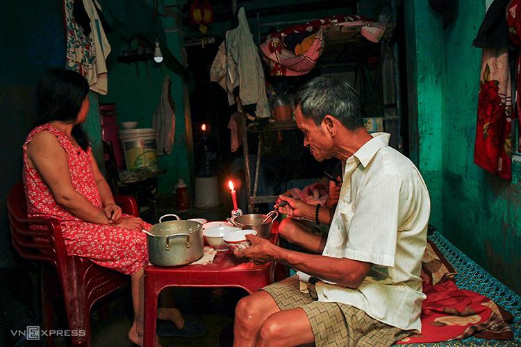 Gia đình ông Khánh thắp nến để sinh hoạt sau gần một tuần lũ chồng lũ, giàn giáo kê tạm chưa được tháo để phòng cơn bão sắp tới. Ảnh: Nguyễn Đông.