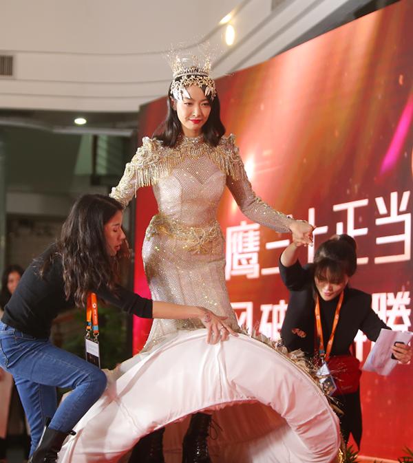 Nhân viên giúp đỡ Tống Thiến di chuyển trên thảm đỏ. Ảnh: Sohu.