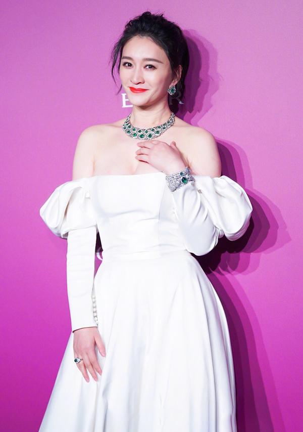 Lý Tiểu Nhiễm diện váy cúp ngực tay bồng kết hợp trang sức màu lục bảo. Ở tuổi 44, diễn viên vẫn giữ được nét tươi trẻ và dáng vóc thon gọn. Theo Sina, nhiều năm trở lại đây, cô ít đóng phim nhưng đắt show sự kiện, chụp ảnh tạp chí.