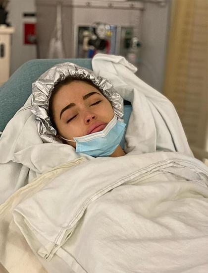 Olivia Culpo nằm nghỉ trên giường mổ sau ca phẫu thuật dài ba tiếng. Ảnh: Olivia Culpo Instagram.