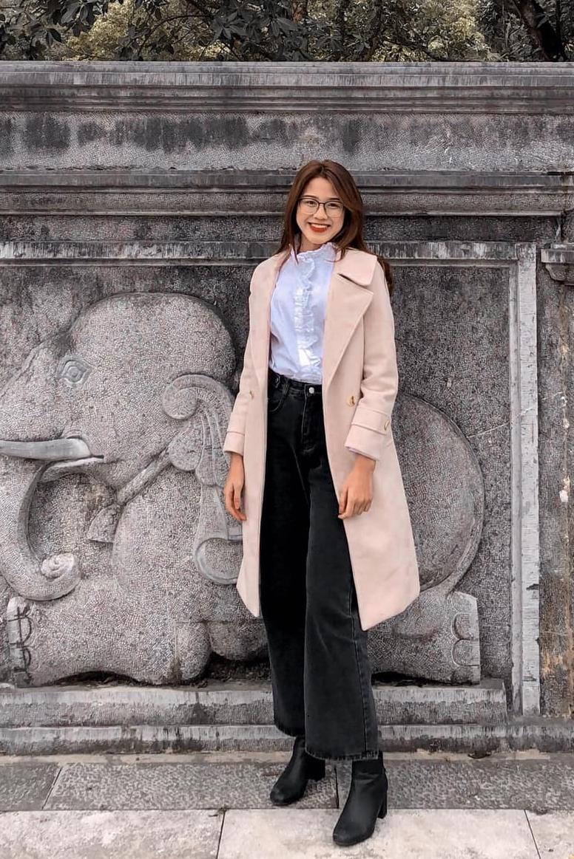 Cô phối đồ mùa động với măng-tô, sơmi và quần jeans ống rộng.
