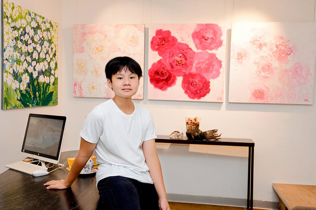 Họa sĩ 13 tuổi Xèo Chu bên các bức tranh tại triển lãm. Ảnh: Lý Đợi.