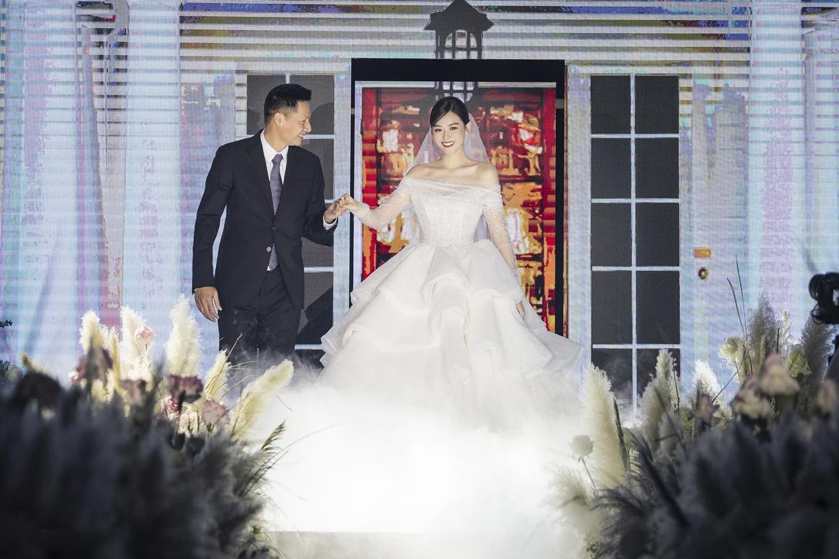 Bố cô dâu dắt con gái bước ra từ sân khấu chính xuống khán đài, nơi chú rể đứng đợi.