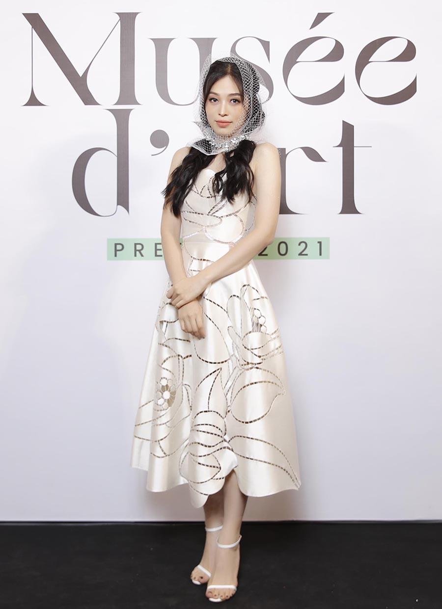 Á hậu Phương Nga là một trong những người đẹp diện váy của Trần Hùng tới thưởng thức show Pre-Fall 2021 Musée d'Art. Bộ váy gây ấn tượng từ những mảnh vải được cắt theo hình cánh hoa, lá cây rồi ghép lại với nhau. Cô phối trang phục cùng khăn lưới trùm đầu.