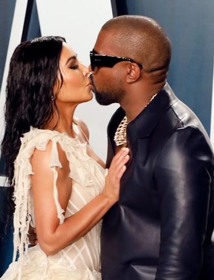 Kim Kardashian (trái) hôn chồng Kanye West trên thảm đỏ bữa tiệc sau lễ trao giải Oscar hồi tháng 2/2020. Ảnh: Vanity Fair.