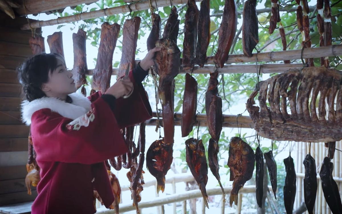 Lý Tử Thất bên các loại thịt, cá khô, hun khói. Ảnh: Weibo Lý Tử Thất.