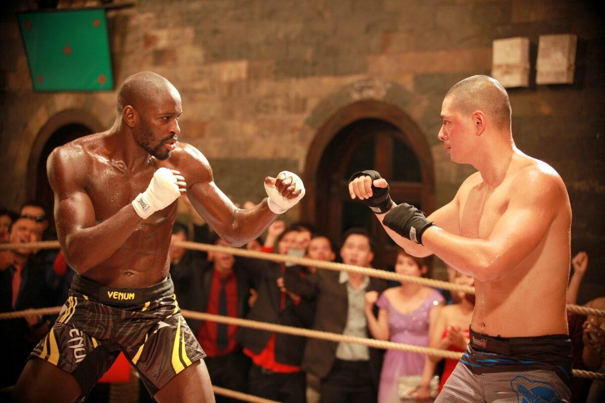 Bình Minh (phải) đối đầu với võ sĩ Thụy Điển Sadibou Sy, trong một cảnh kịch tính của phim Sám hối. Phim khai thác tốt các ngón đòn đấm, đá, khóa tay của bộ môn võ tự do (MMA). Ảnh: Ánh Sao.