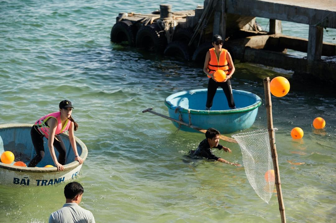 Các người đẹp loay hoay tìm cách vừa ném bóng vào rổ, vừa giữ thăng bằng cho chiếc thuyền thúng.